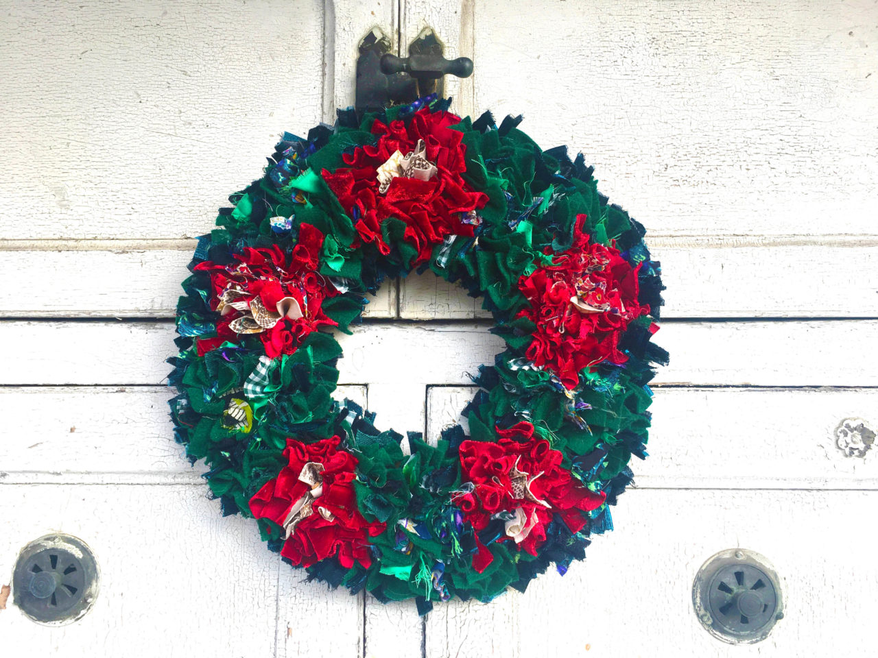 Traditional red and green rag rug christmas wreath made of old clothing with a rag rug spring tool