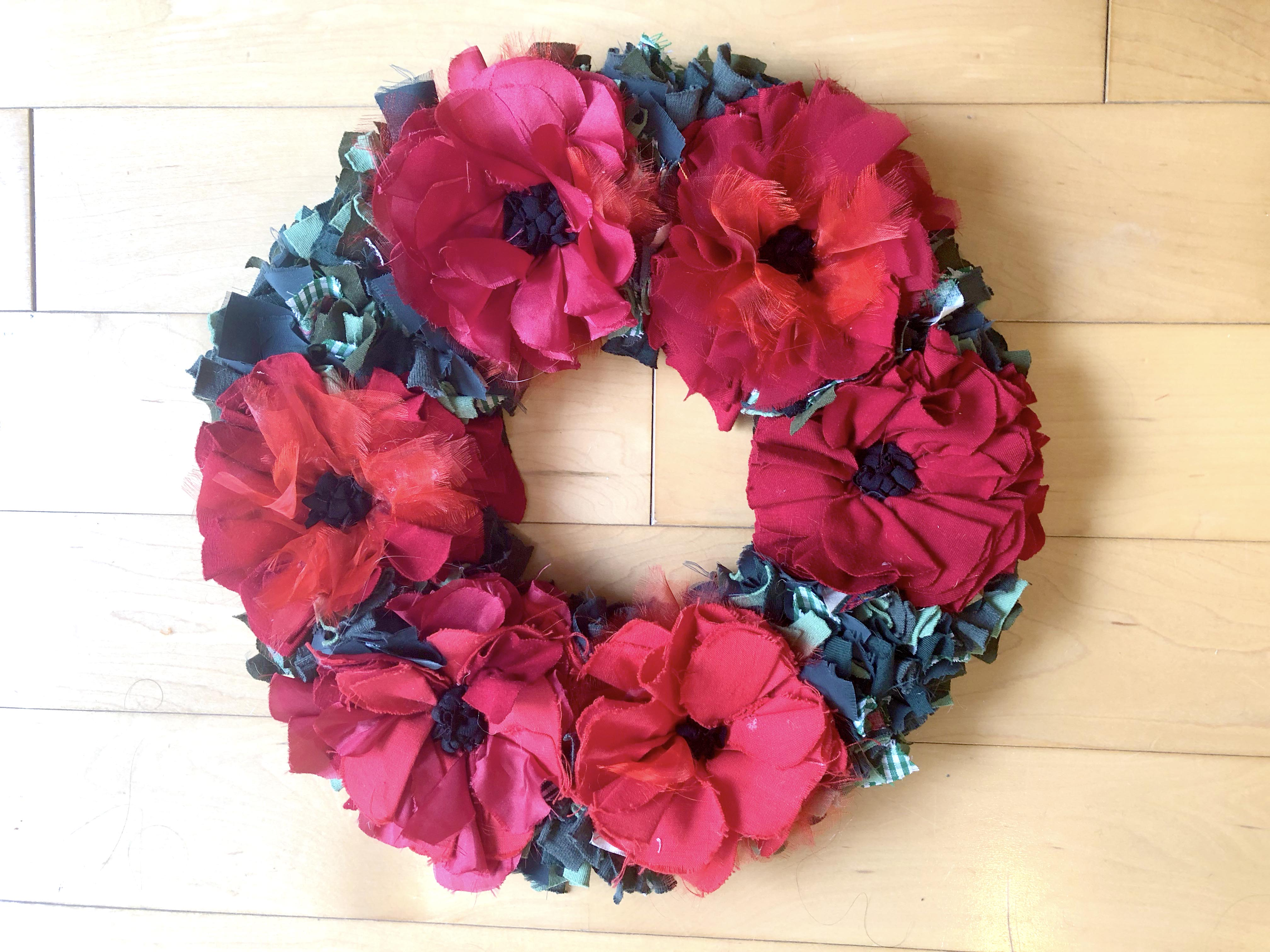 Remembrance day rag rug poppy wreath made using recycled textile waste. Red poppies with green fabric in between.