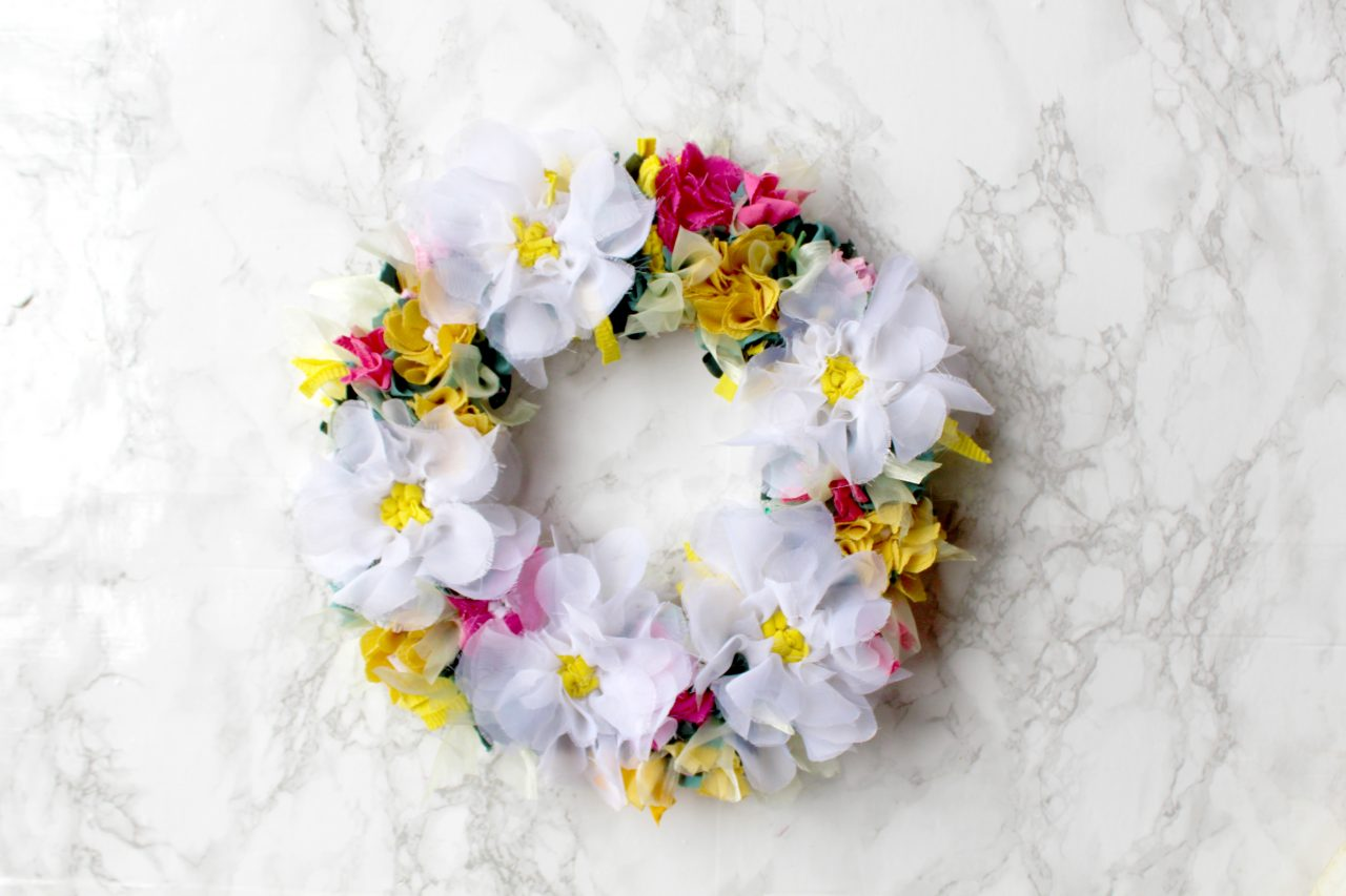 Ragged Life spring rag rug wreath made using recycled material with white flowers and pink and green foliage.
