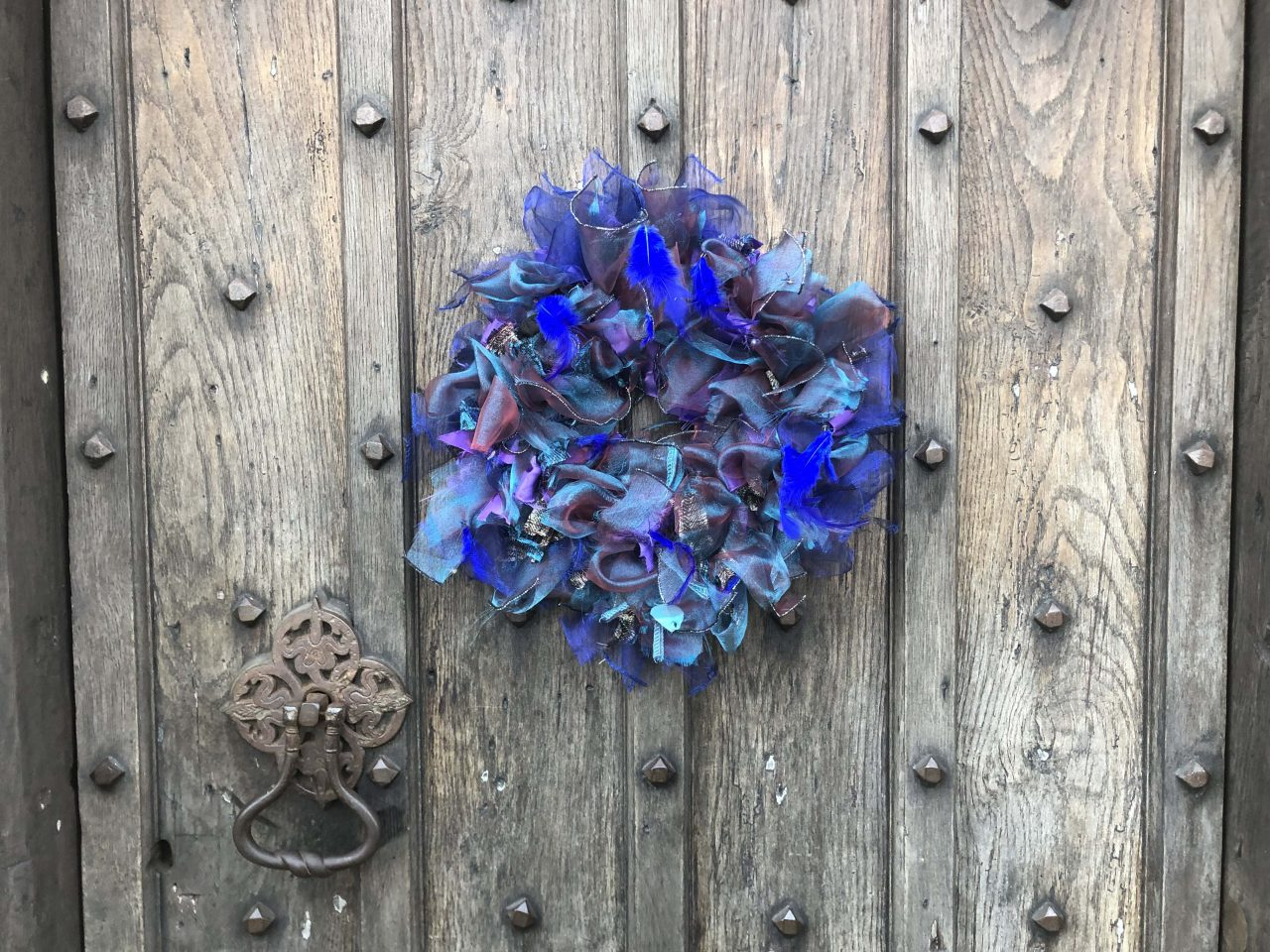 Purple and blue upcycled rag wreath made using an old halloween costume with feathers and shiny voile.