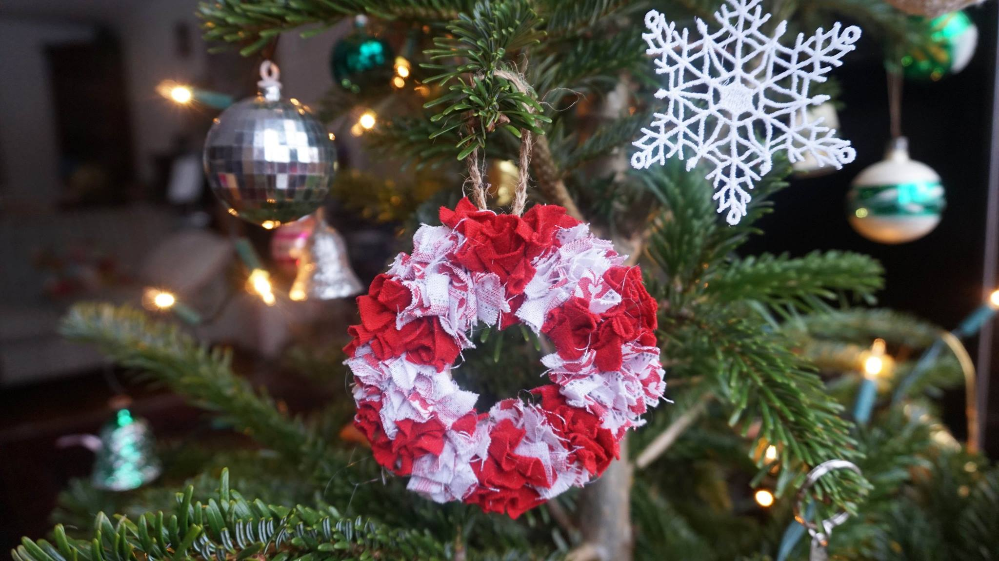 Mini rag rug wreath hanging from a Christmas tree in red and white candy cane stripes.