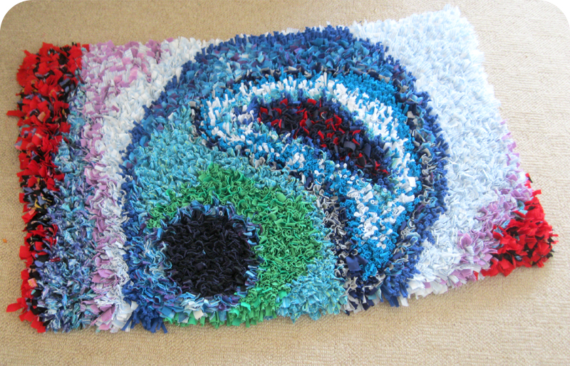 Abstract swirl rag rug with blues, greens and reds made in the proggy technique using old t-shirts