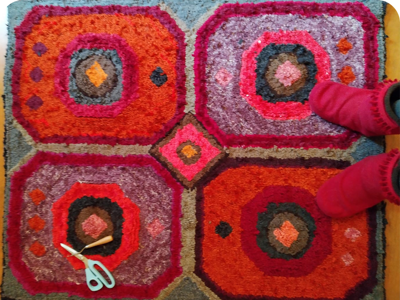 Red and purple hooked rag rug with latch hook and rag rug scissors
