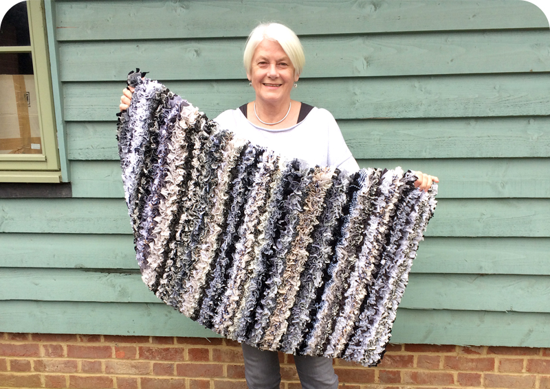Julia holding her Scandinavian inspired black and white striped neutral rag rug for her daughters home in Stockholm