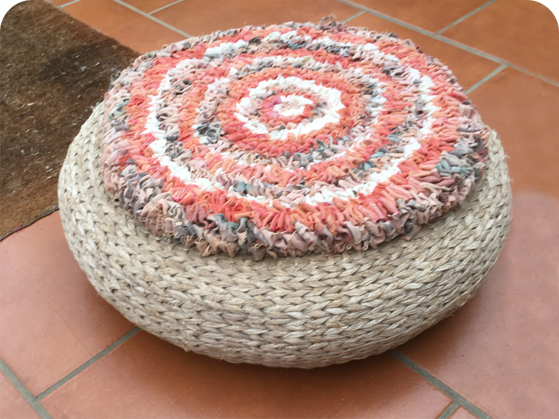 Loopy or hooky rag rug circular footstool in orange, cream and brown