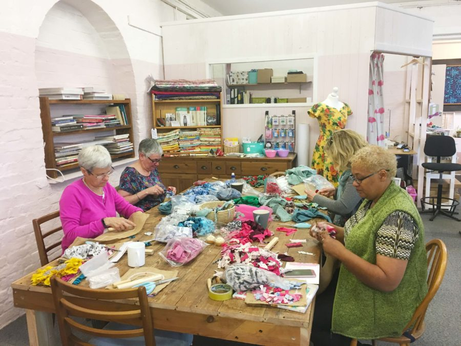 A group of ladies rag rugging at a table in a rag rug workshop at the Craft Space in Wiltshire