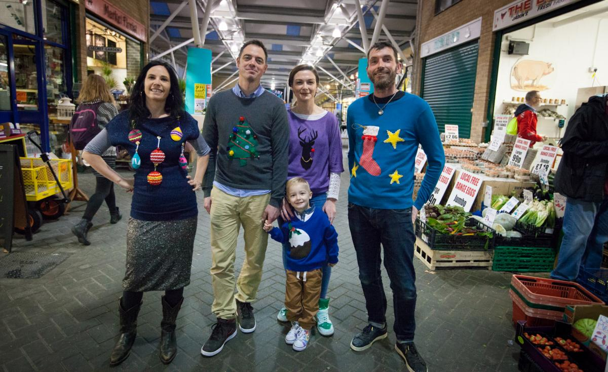A group of happy people wearing handmade Christmas jumpers in a market