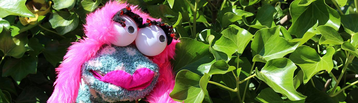 A sock puppet with large eyes and pink lips and hair