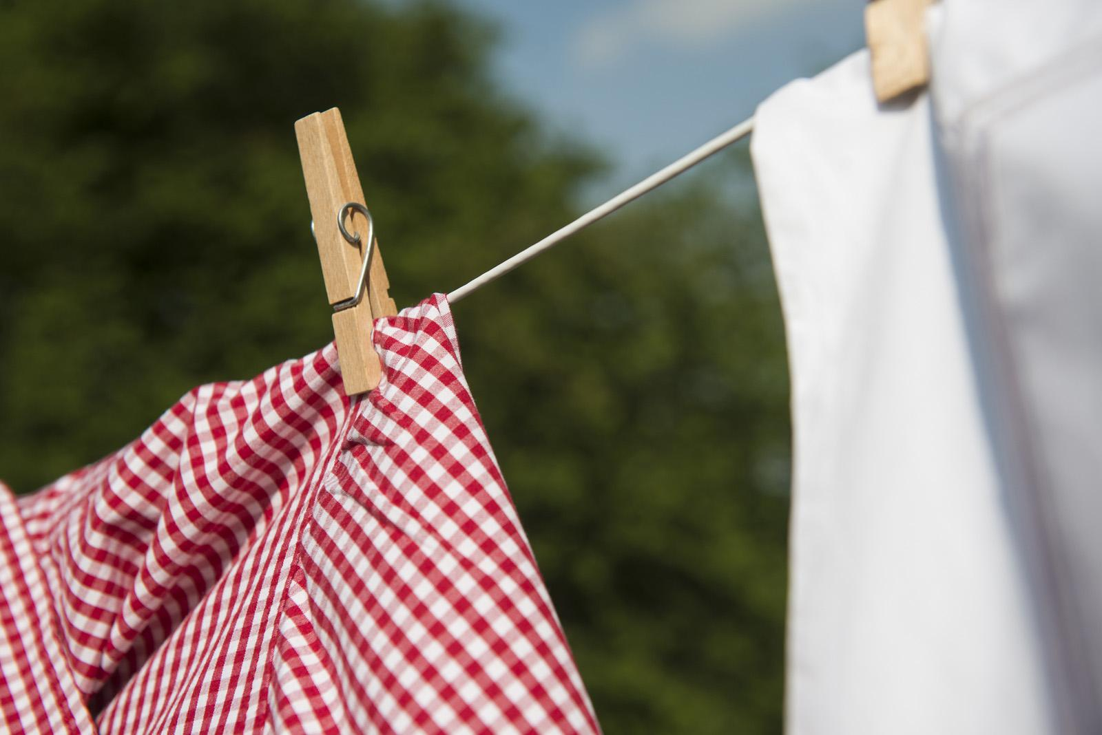 A red gingham apron on a washing line with wooden pegs
