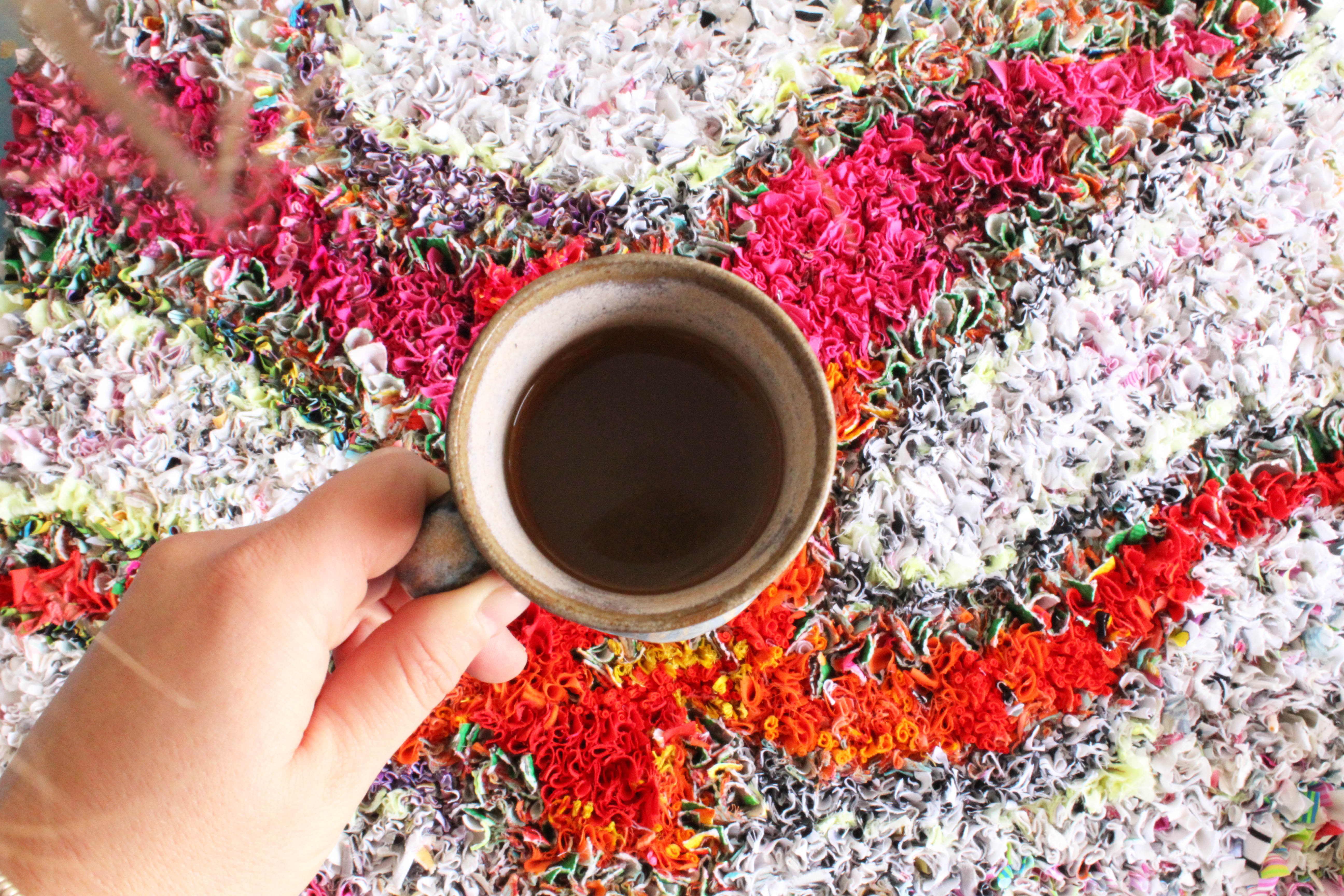 A cup of coffee on top of a colourful shaggy rag rug