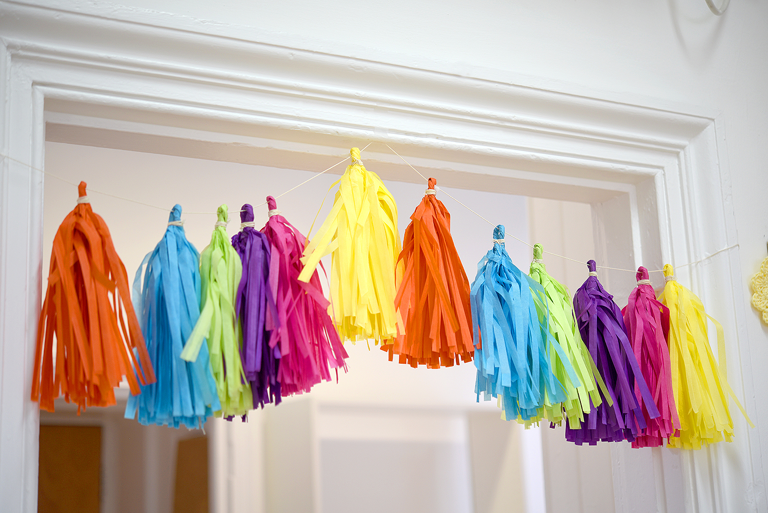 Multi-coloured Handmade Paper Tassels hanging above the door at Tea and Crafting's new workshop space