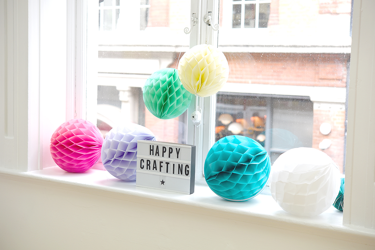 Paper lanterns in front of the large window with happy crafting lightbox