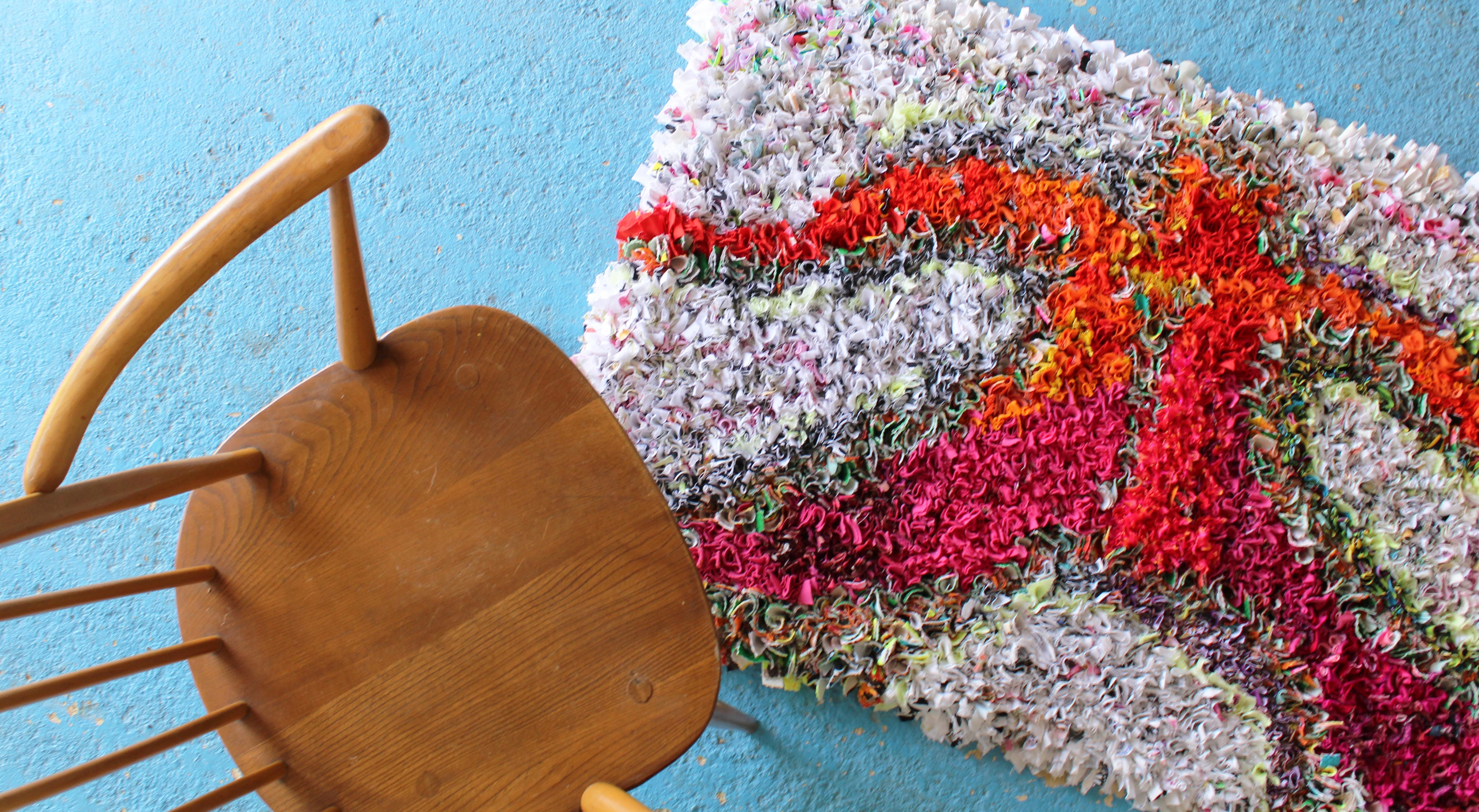A Ragged Life rag rug on a blue floor with a wooden Ercol chair