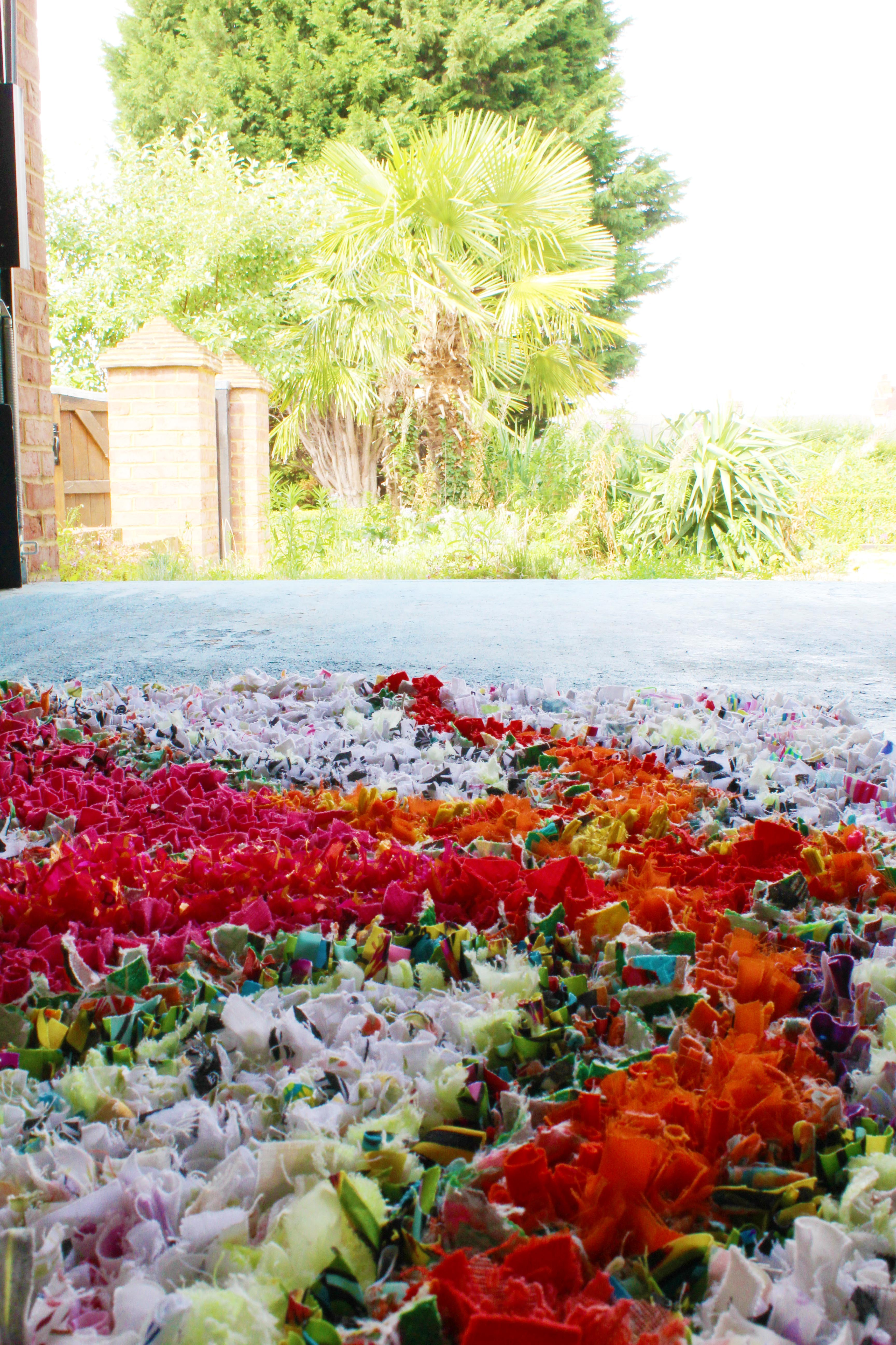 Close up of bright rag rug from the side with trees in the background and a blue floor
