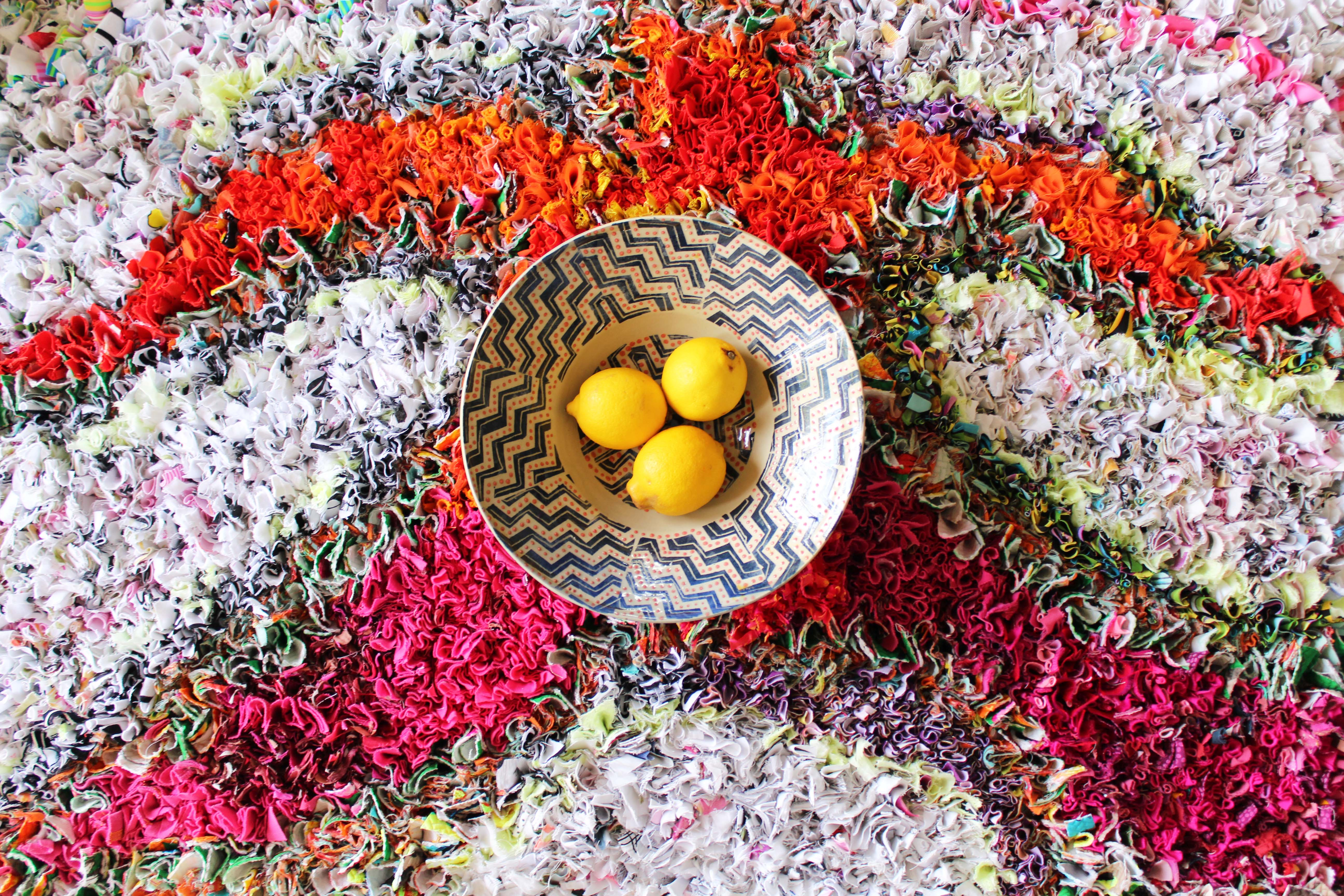 A bowl of yellow lemons in the centre of a finished rag rug