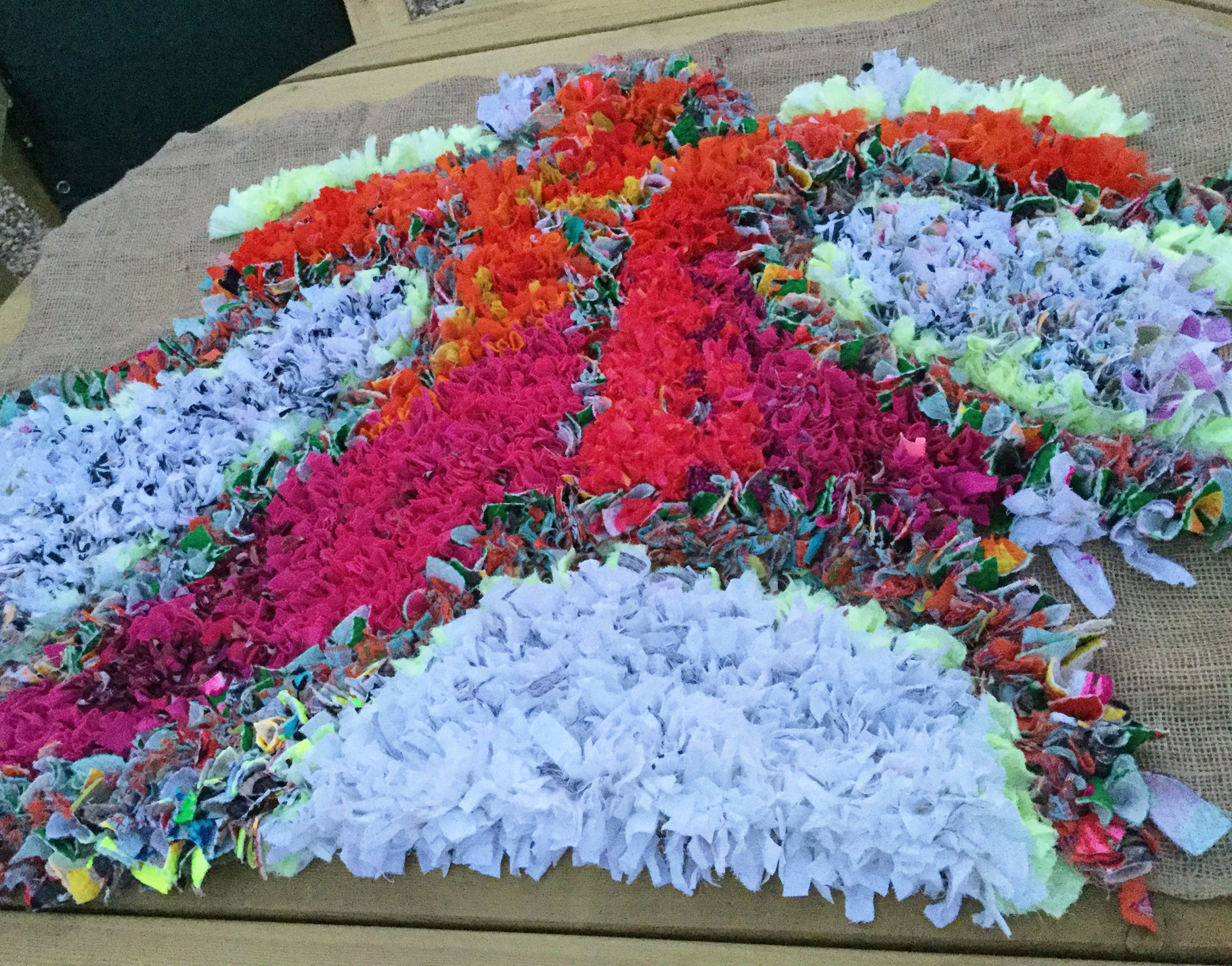 A work in progress photo of a proggy rag rug with white, orange and pink