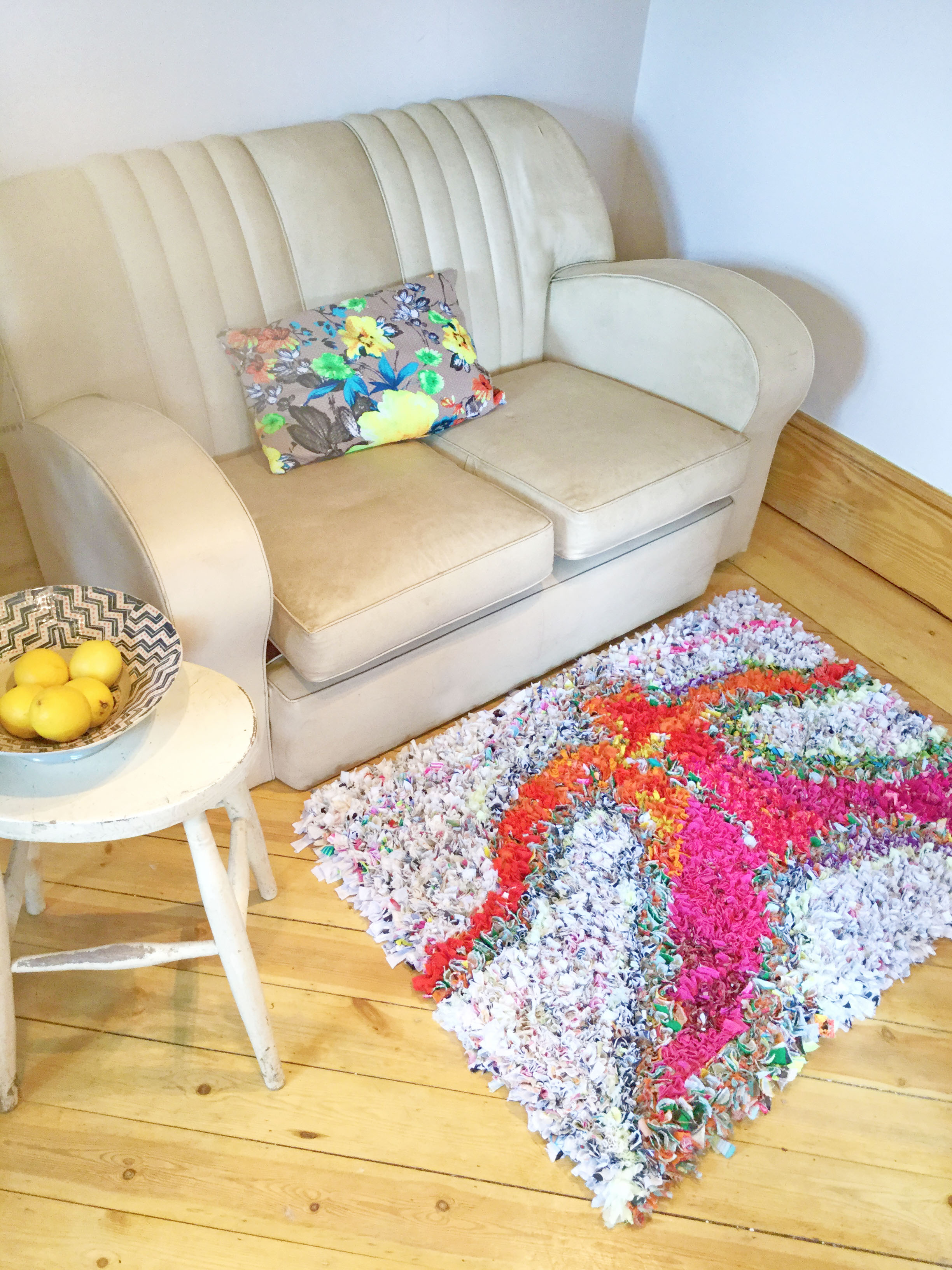 A unique rag rug in front of a white vintage sofa on a wooden floor