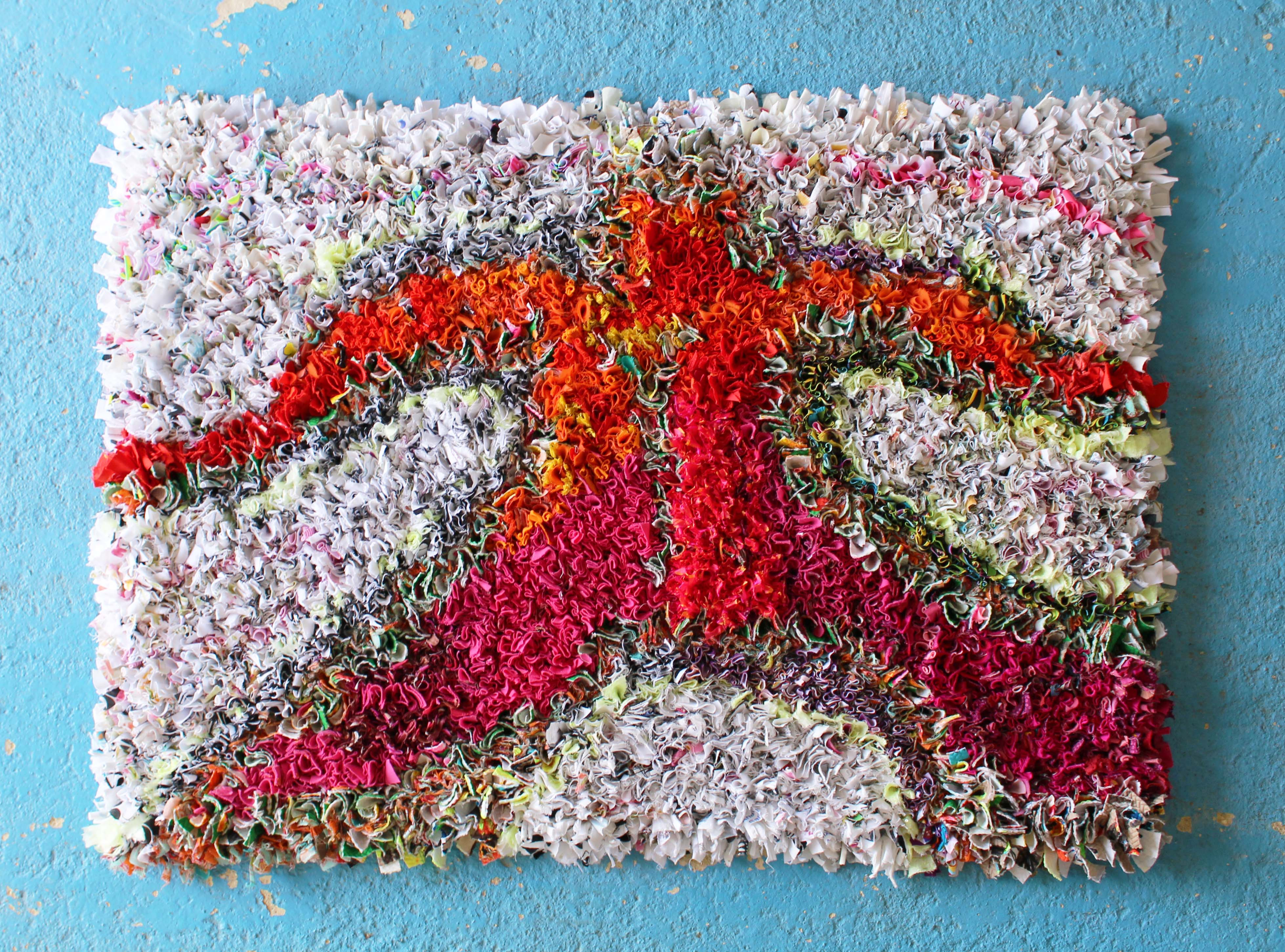 Beautiful rag rug shaped like a person in the shaggy rag rugging technique with orange and pink