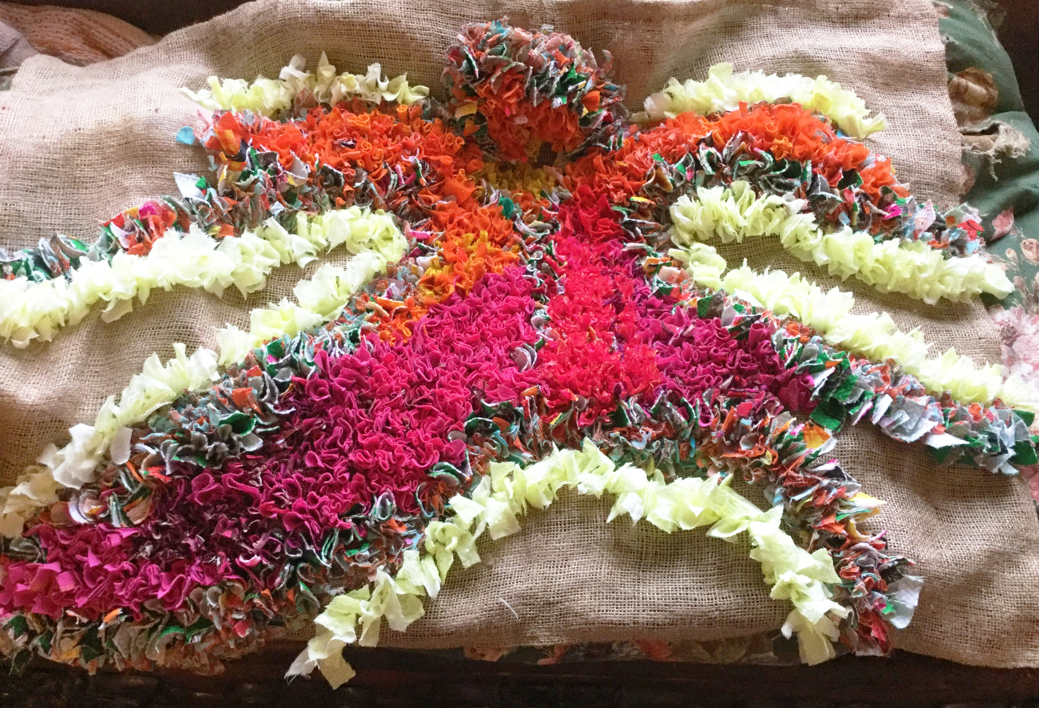 A half made beautiful rag rug with pink orange done in the proggy style