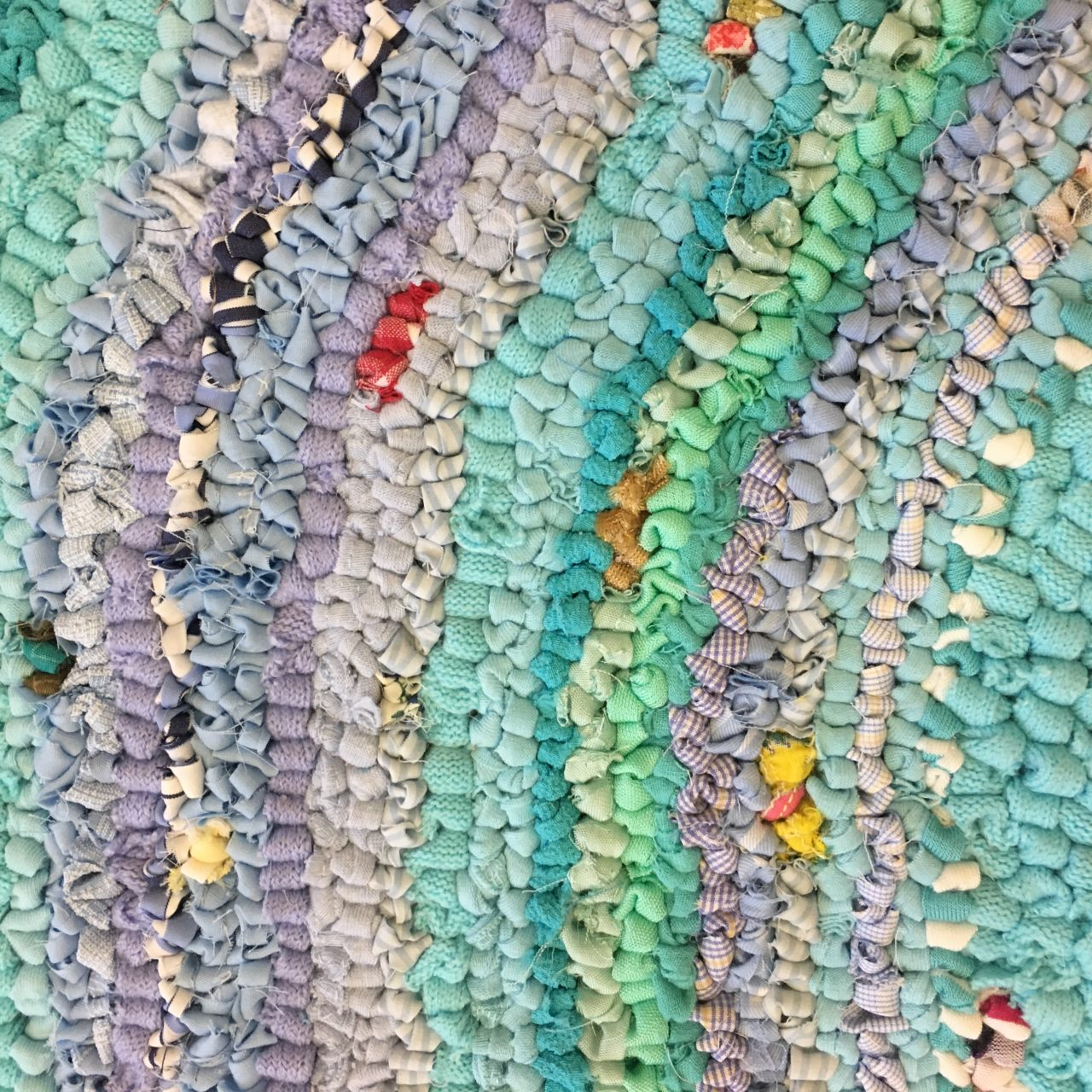 Stripes of blue hooky rag rugging in a rag rug wall hanging piece of art