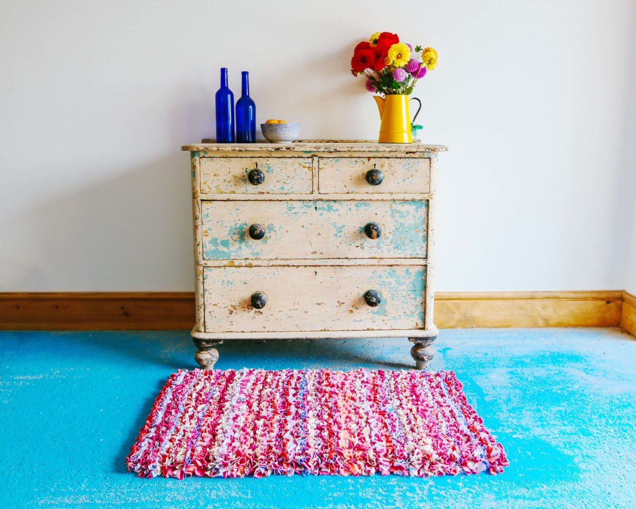 Ragged Life Pink Striped Rag Rug in front of chest of drawers