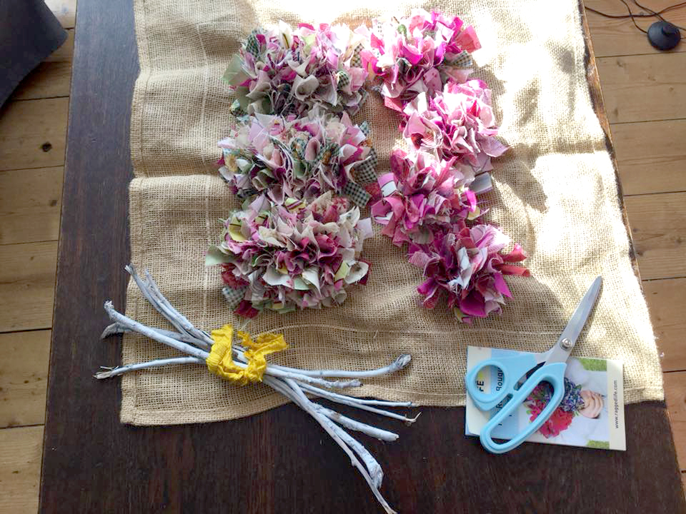 Unassembled rag rug bouquet kit with seven flowers and flower stems and ragged life rag rug scissors