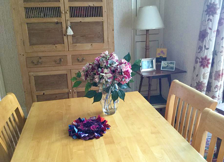 Cotton rag rug flowers in a bouquet on a table with a rag rug trivet