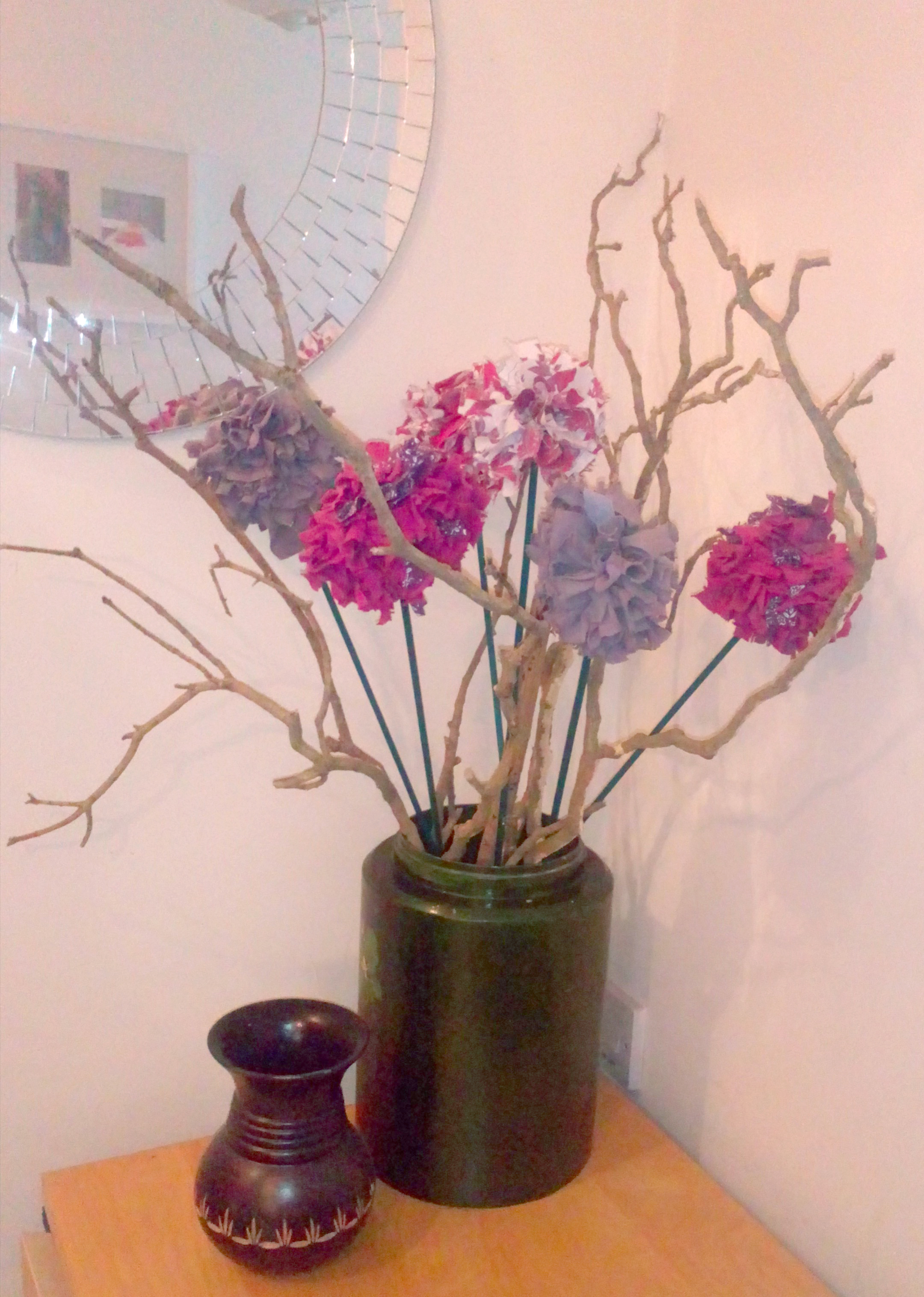 Pink fabric flowers in a green vase with wooden twigs