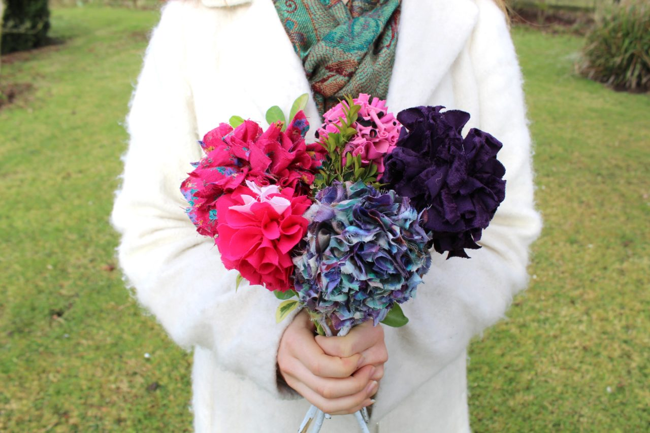 Upcycled fabric rag rug bouquet of rag rug flowers held in hands outside