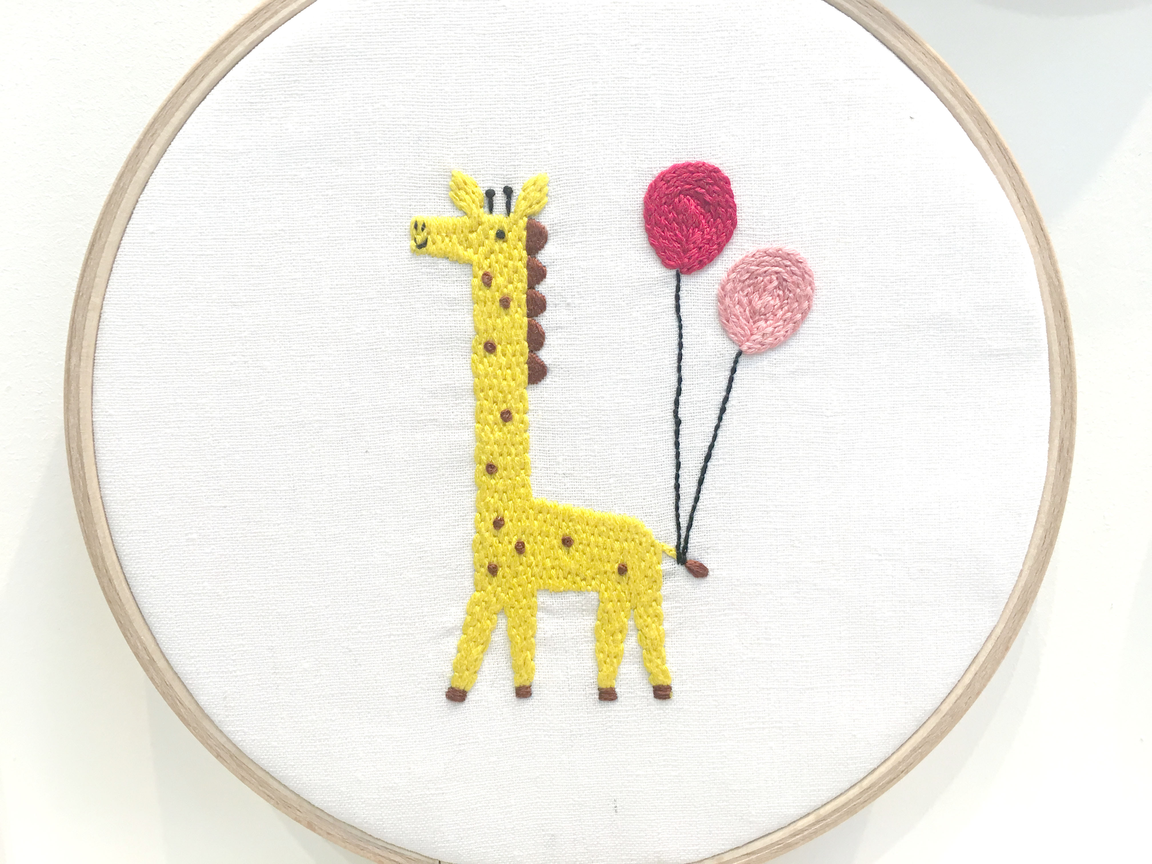 Yellow embroidered giraffe with balloons
