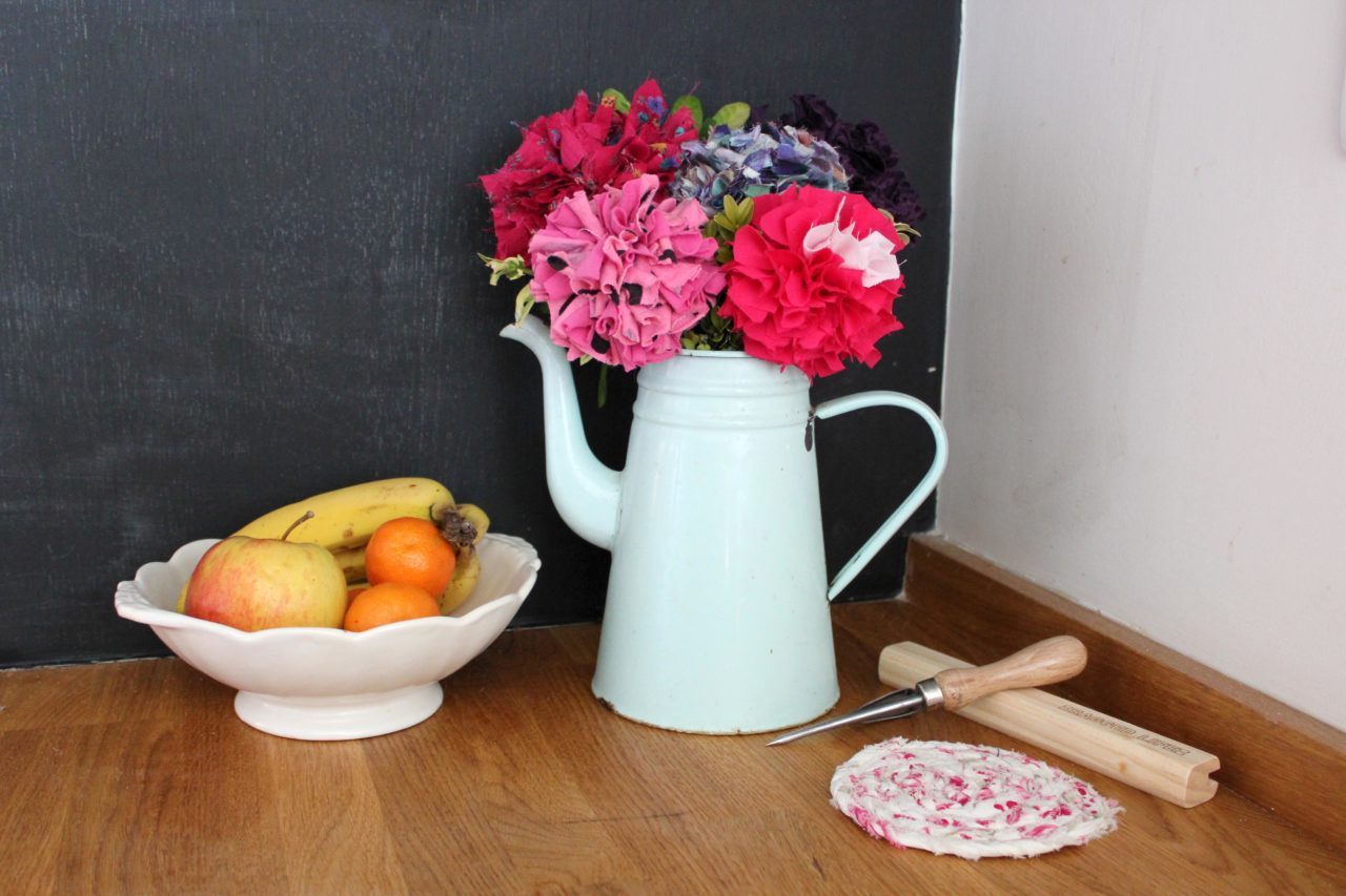 Rag Rug Flowers in a bouquet in a blue coffee pot in front of a chalkboard with rag rug spring tool