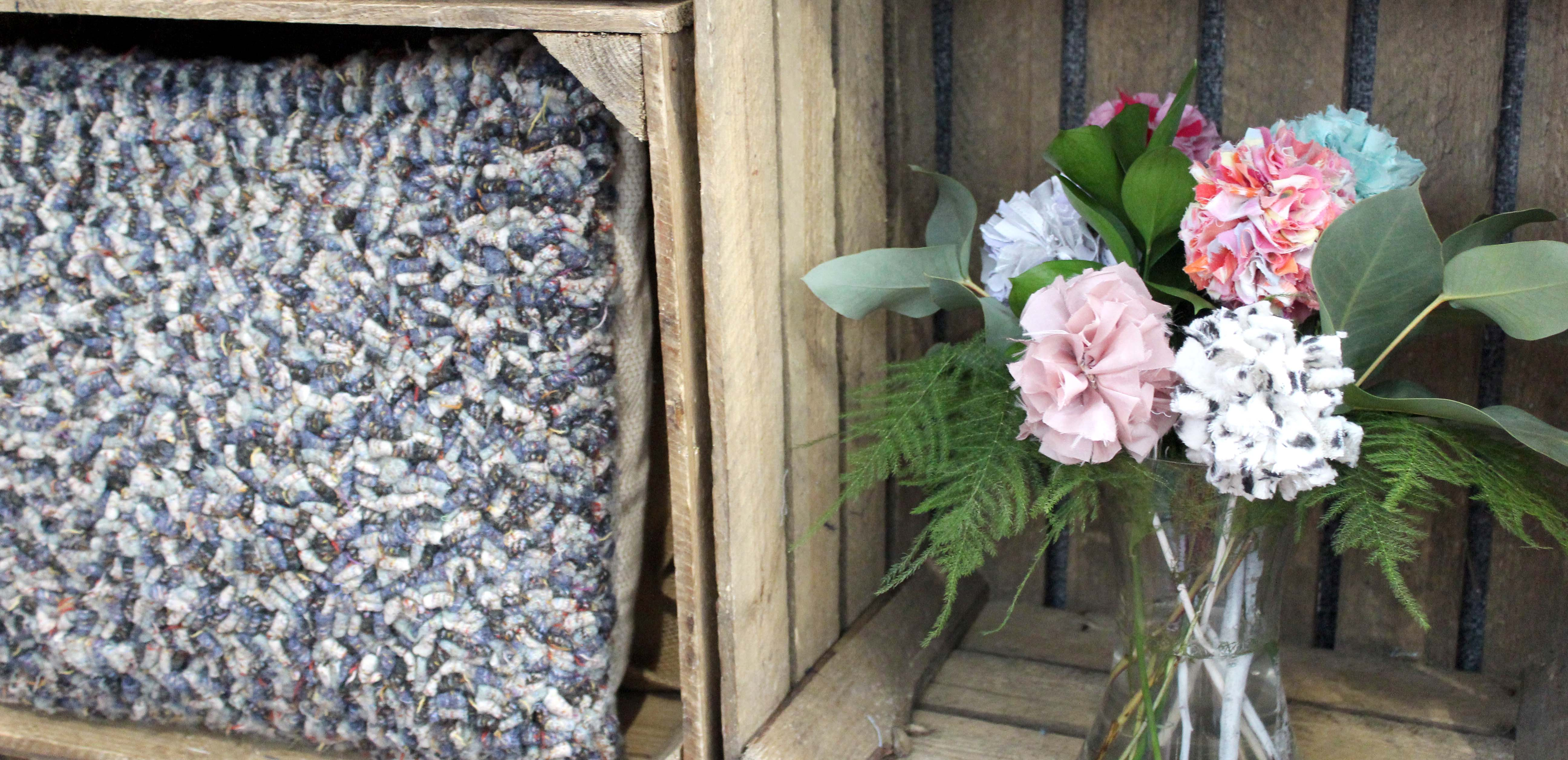 Rag Rug Cushion and Flowers in wooden crates