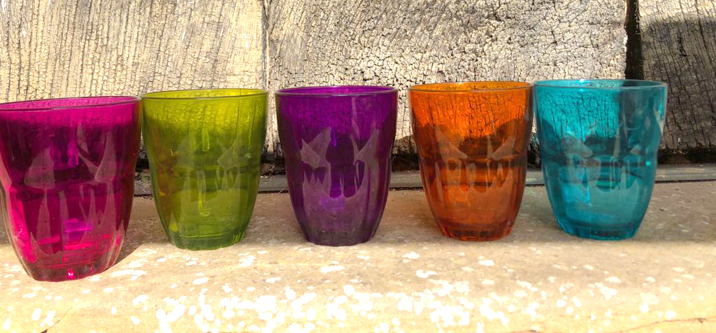 Colourful water glasses in a row