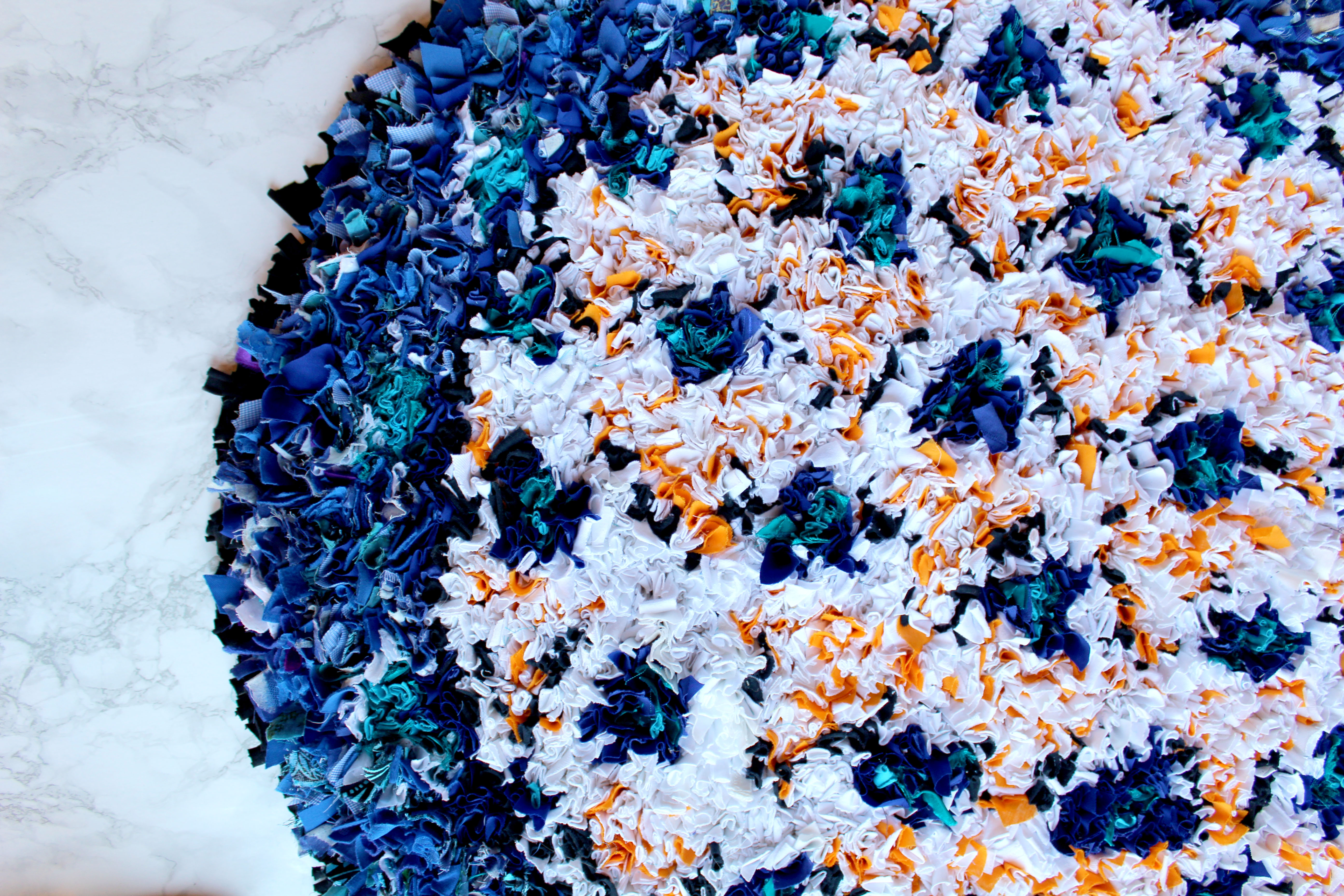 Circular shaggy rag rug in blue, white and orange with triangles of colour