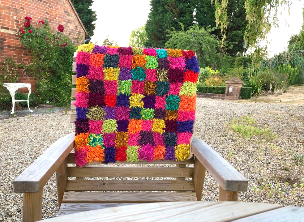 Rag rug on chair in garden in checked design with squares