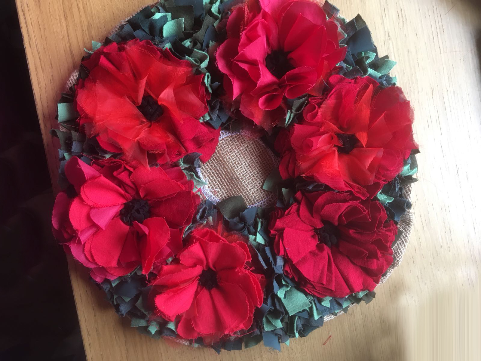 rag rug poppy wreath in red and green made using recycled fabrics