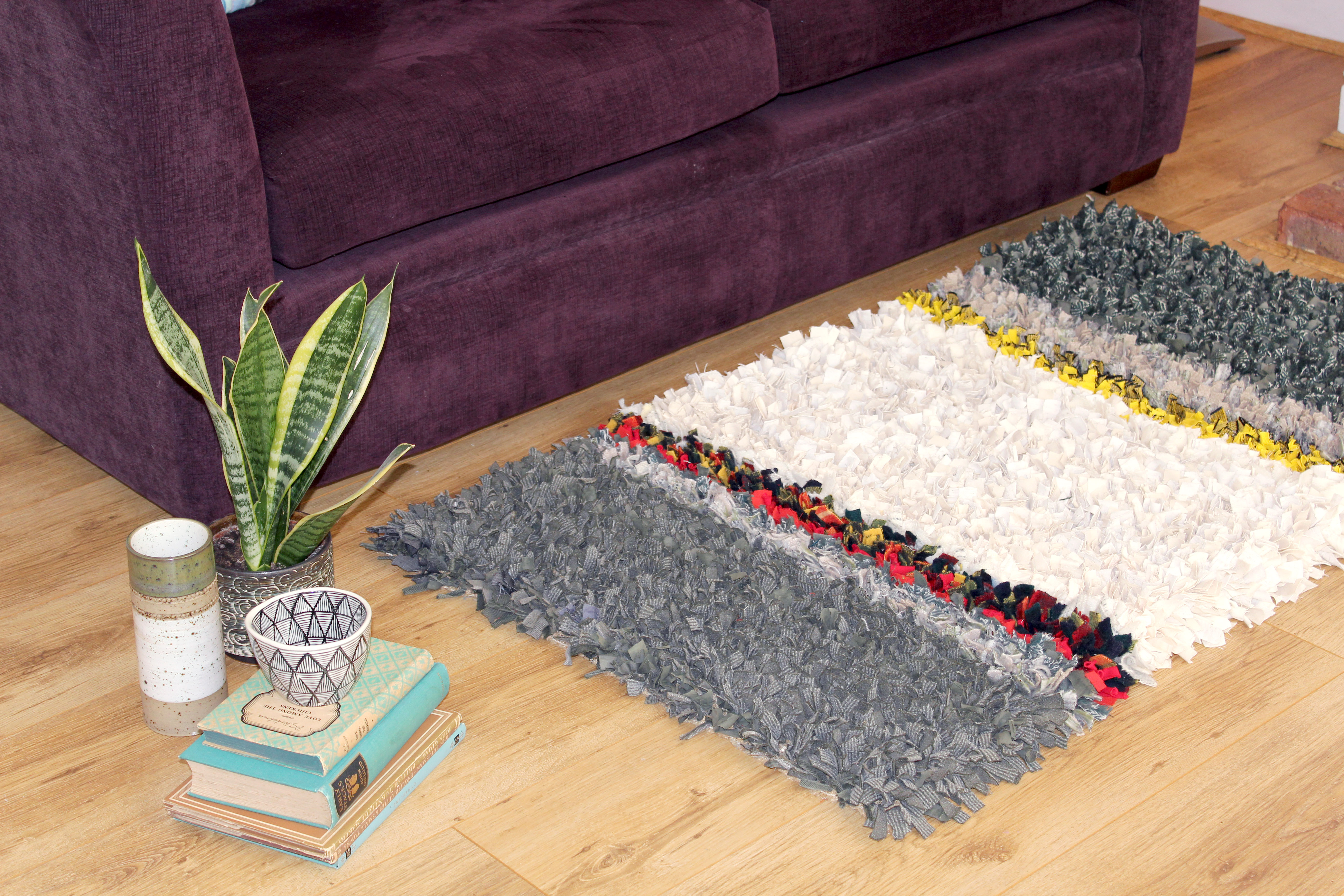 Rag rug made by hand in front of sofa in grey, red, yellow and green colours.