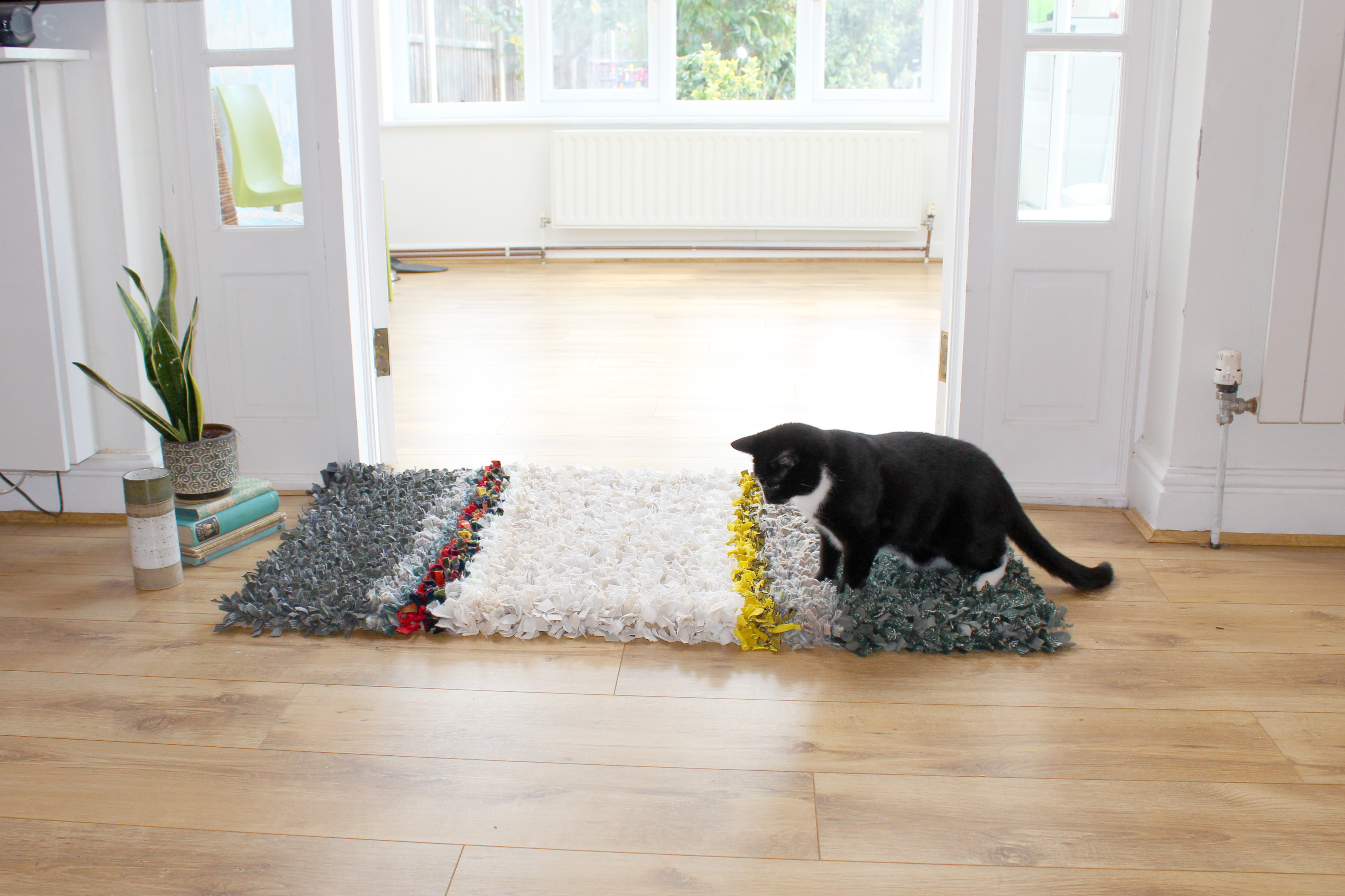 Striped handmade rag rug with cat sitting on it