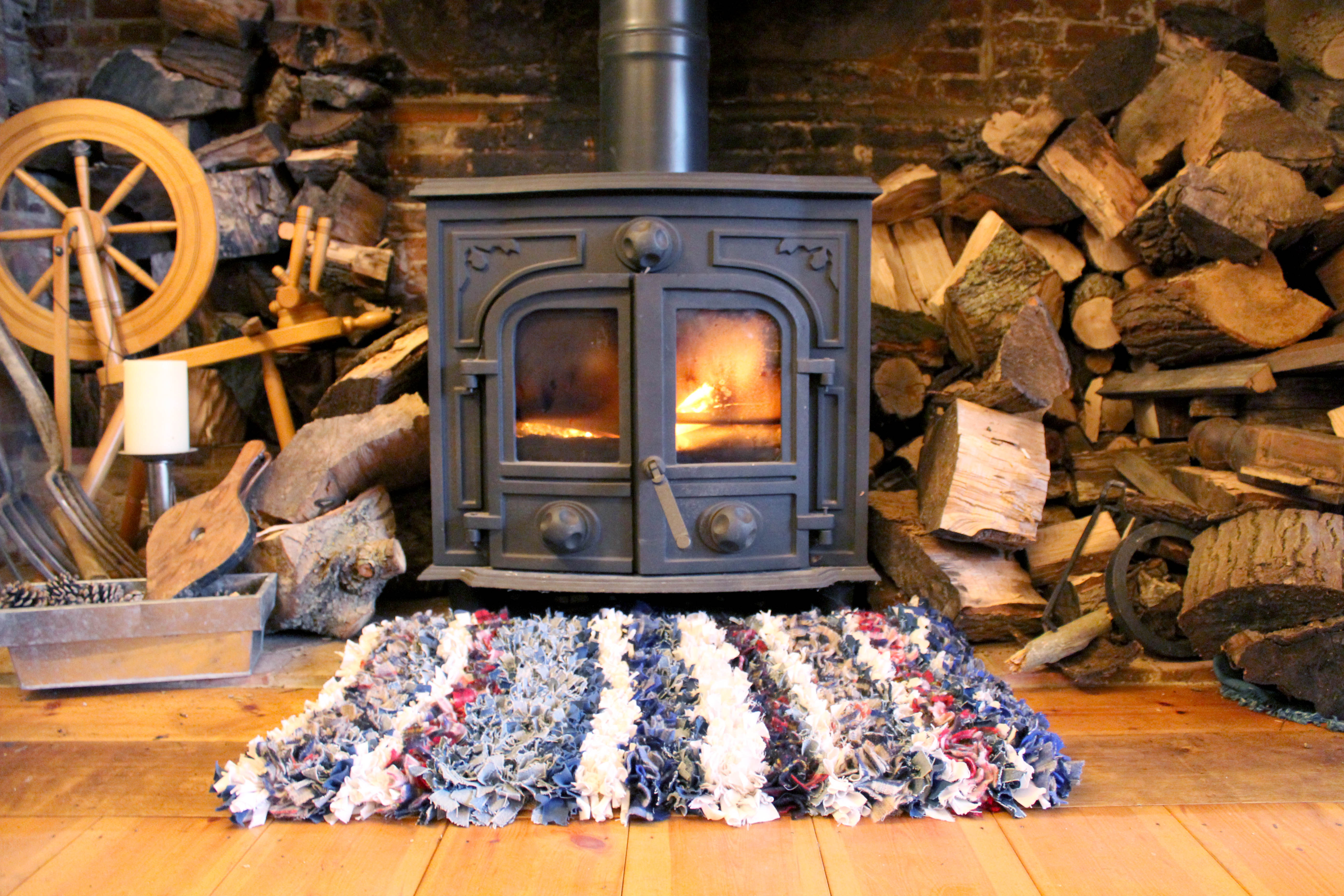 log burning stove with striped cosy rag rug with live fire