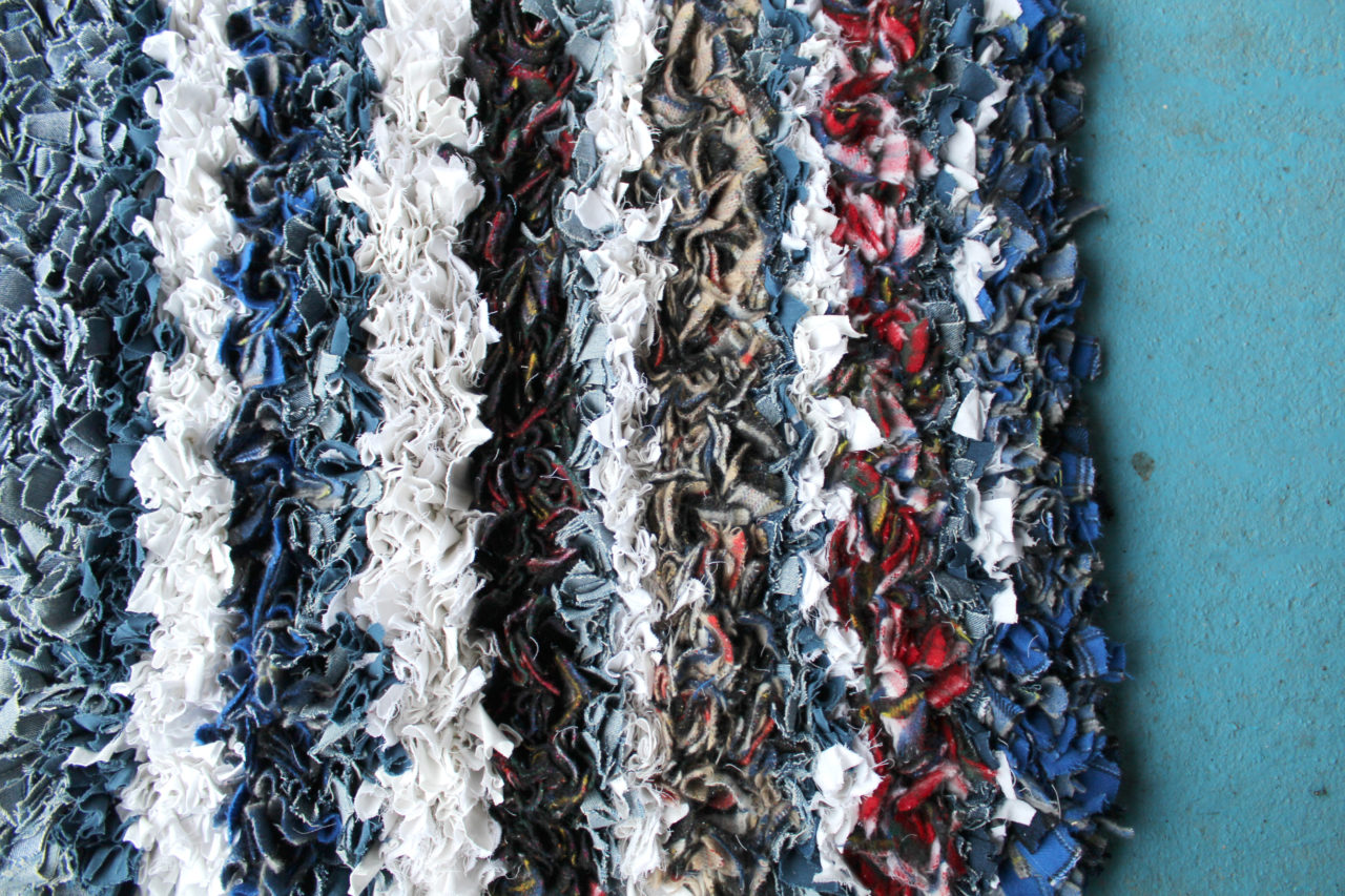 Stripes of white, grey, blue and red fabric for rag rugs