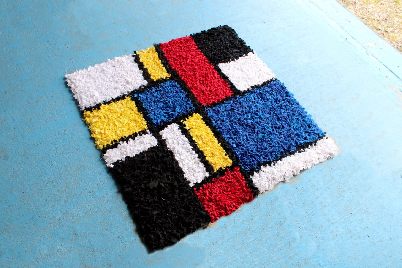 Large Mondrian Inspired Rag Rug Design on a Blue floor with red, yellow, blue, black and white geometric blocks of colour