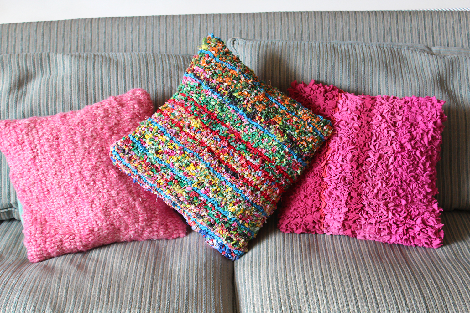 Pink and colourful hooked rag rug cushions on sofa