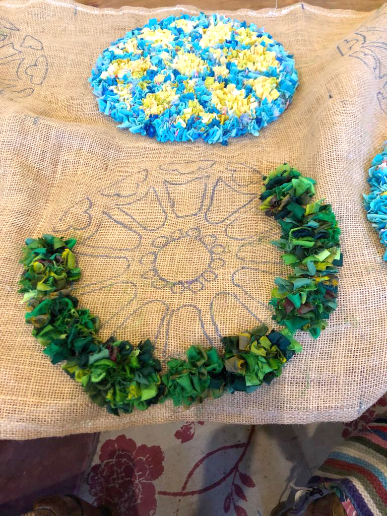 Green rag rug with design sketched onto the hemmed hessian