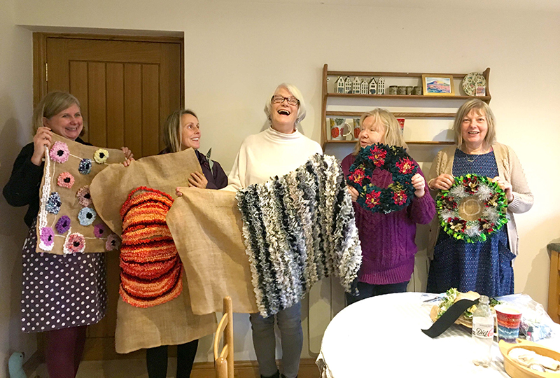 Craft lovers holding up their rag rug creations at the Hertfordshire Ragged Life Rag Rug Coffee
