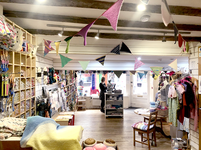The inside of Knit & Stitch craft shop in York with knitted bunting and rag rug workshops