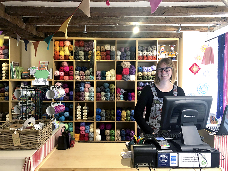 Knit and Stitch York craft shop till with shelves of wool behind