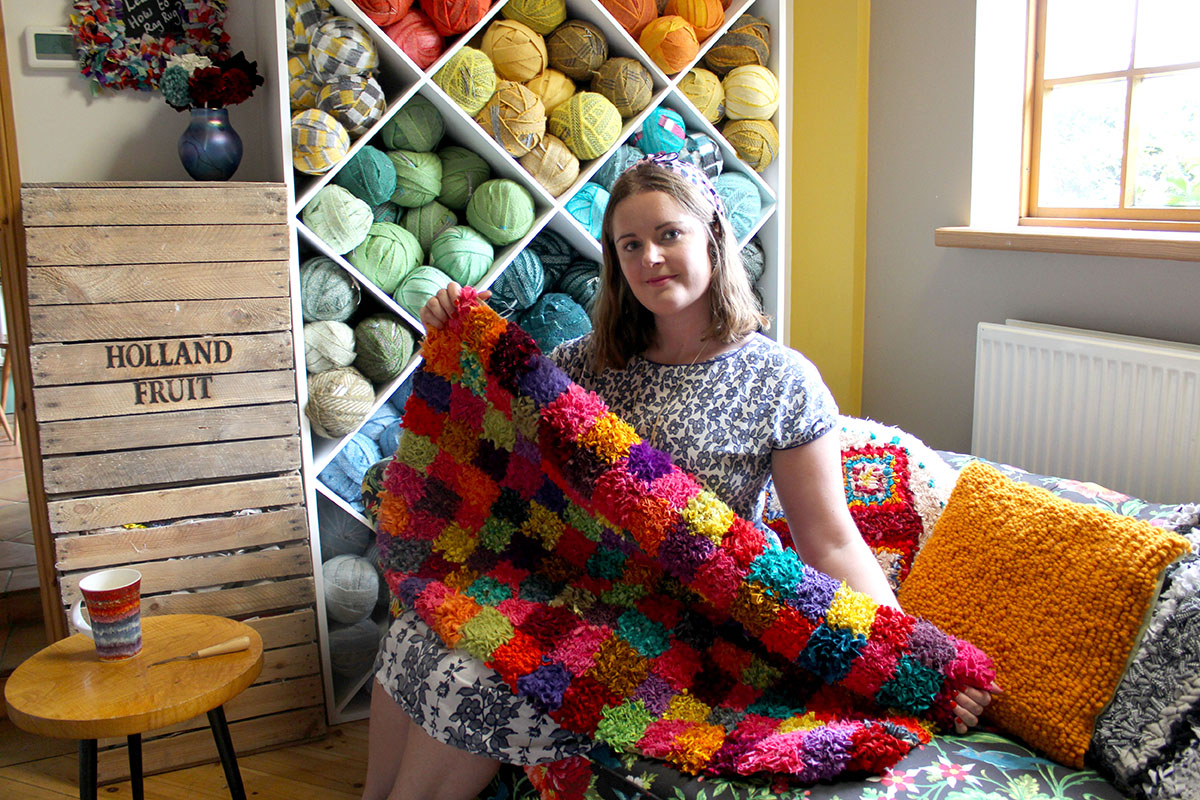 Elspeth Jackson making a rag rug in front of her wall of 100% wool blanket yarn