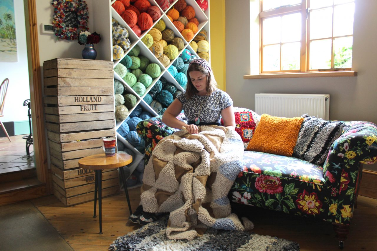 Elspeth Jackson from Ragged Life making a rag rug on a sofa