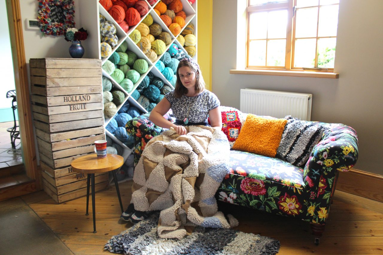 Elspeth Jackson from Ragged Life rag rugging on a sofa with rainbow blanket yarn