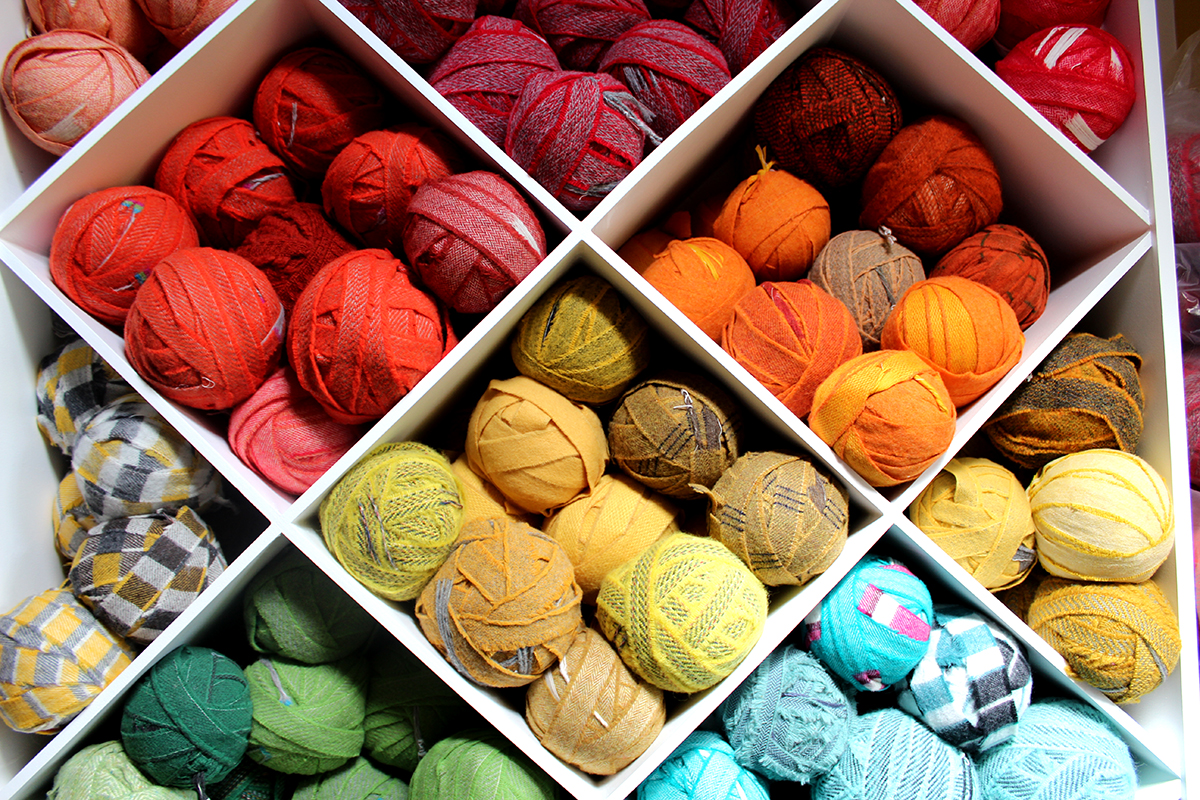 Red, orange and yellow blanket yarn for rag rugging stacked into custom made craft shelving